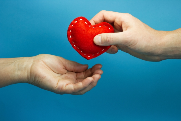 Man hand puting the red soft heart in woman hand