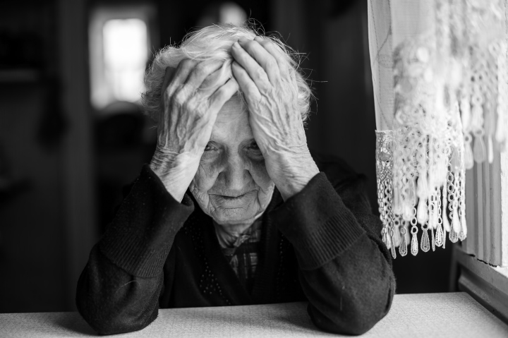 Elderly woman sitting at the table in a depressed state,